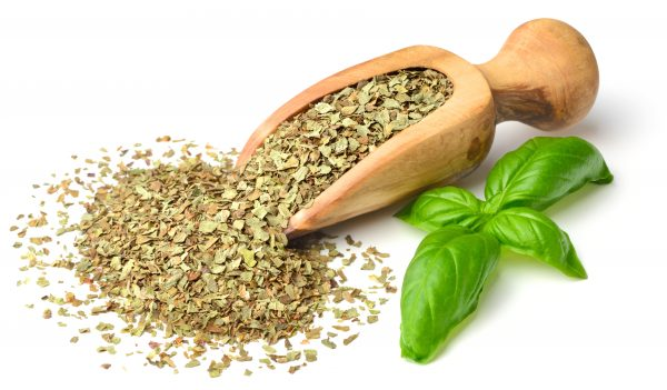 dried herb, basil leaves in the wooden scoop, isolated on white.jpg