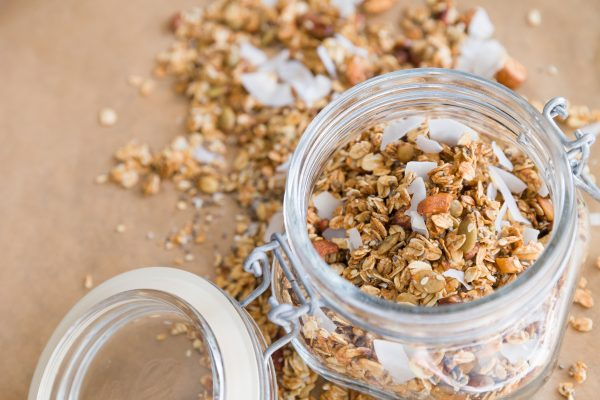 Glass jar of homemade organic granola with coconut and pecans on the baking paper background. Delicious breakfast cereal. Healthy muesli..jpg